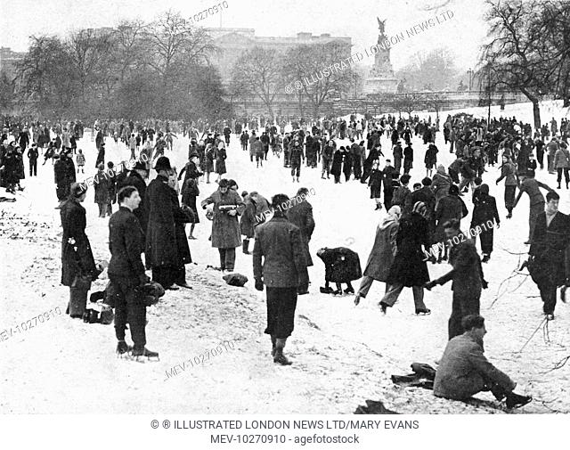 A cheerful crowd disporting on the ice in front of Buckingham Palace. During one of the coldest winters experienced by Britain