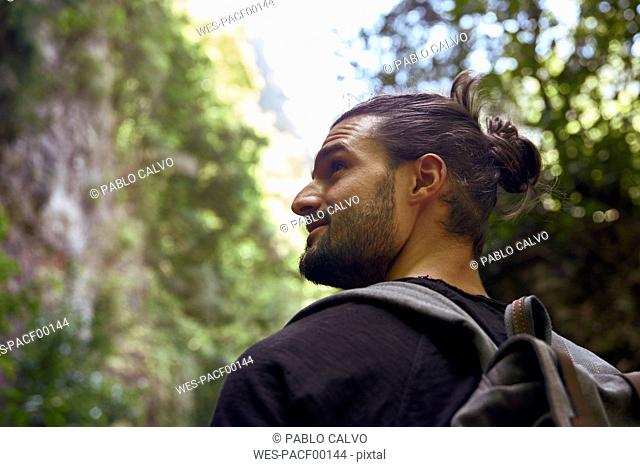 Spain, Canary Islands, La Palma, rear view of hiker in a forest looking around