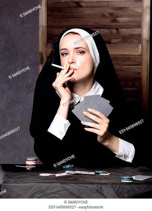 beautiful catholic nun smokes and playing cards. Rotten religion
