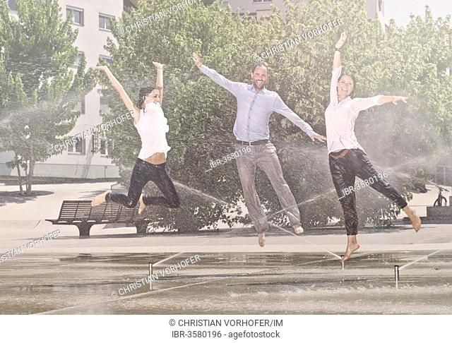 Two women and one man jumping in the park, between water sprinklers