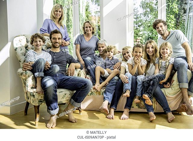 Group portrait of family and friends sitting on sofa in living room