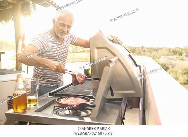 Mature man grilling steaks on a gas grill on his penthouse terrace