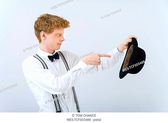 Young man showing magic with hat