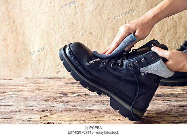 Cleaning shoes on wooden background