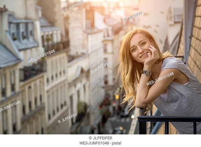 France, Paris, portrait of smiling woman standing on balcony in the evening
