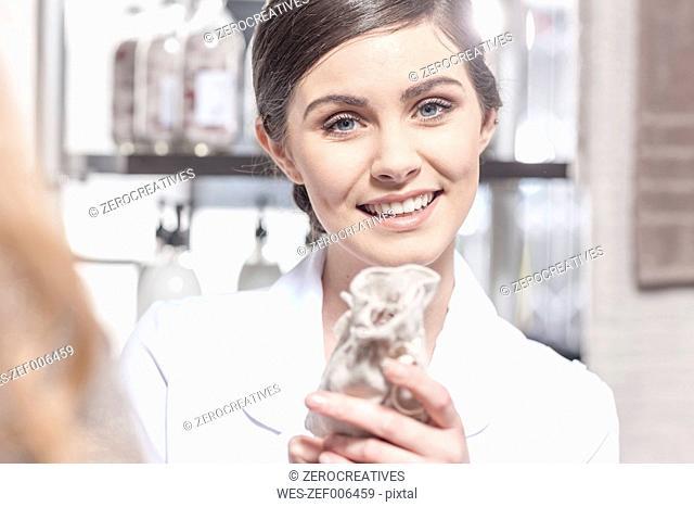 Smiling shop assistant in wellness shop holding sachet