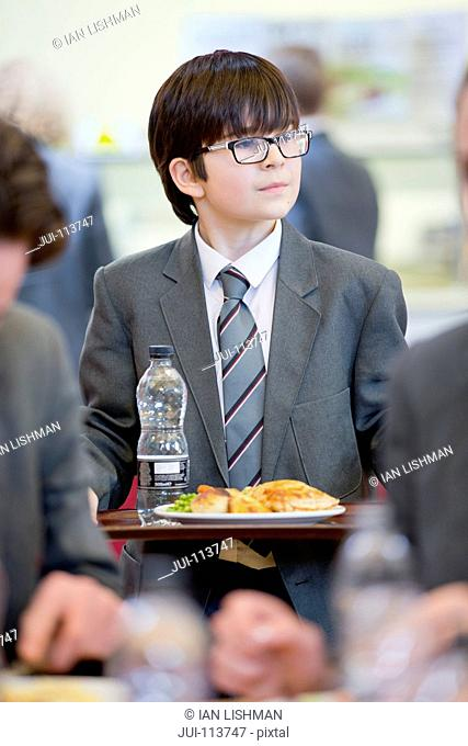 Middle school student eating lunch looking away in school cafeteria