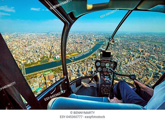 Helicopter cockpit inside the cabin flying on Tokyo city skyline, Sumida River Bridges and Asakusa area. Daytime. Tokyo, Japan