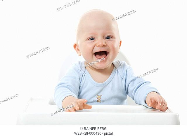 Baby boy 6- 11 Months on high chair, laughing, portrait