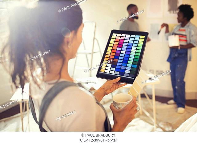Young woman with digital tablet viewing digital paint swatches, painting living room