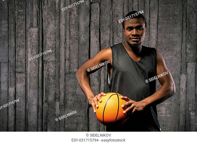 Afro-american young muscular man playing basketball against grunge background and looking at camera