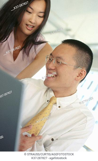 Asian man and woman working at computer in contemporary office