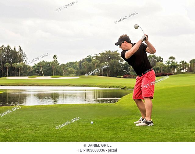 Mid adult man playing golf