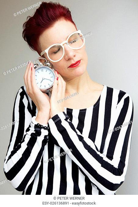 red-haired woman standing and holding alarm clock with her eyes closed