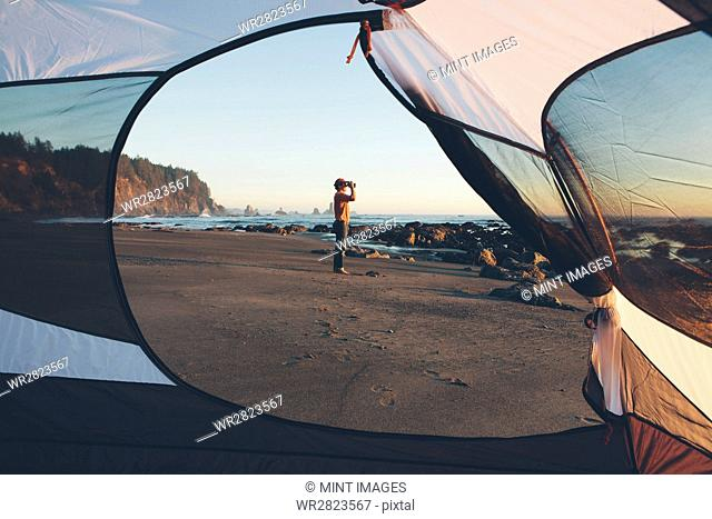 Man framed by camping tent, standing on beach and looking through binoculars at dusk, Olympic National Park, Washington, USA