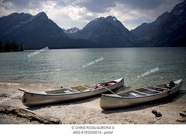 Two canoes are beached on the shore of Lake Leigh with the Grand Tetons in the distance