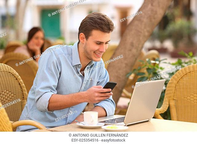 Self employed happy man working with a laptop and a smart phone in a restaurant terrace
