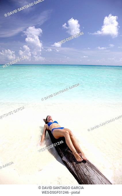 Maldives, woman sunbathing on a log on a beach