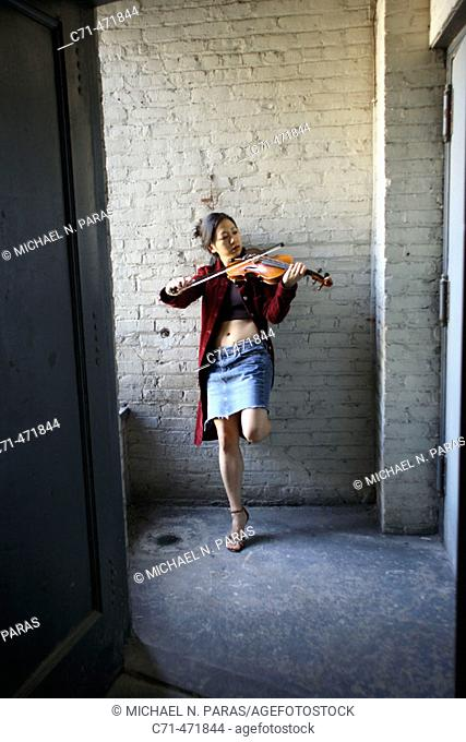Sexy asian woman playing violin in stairwell