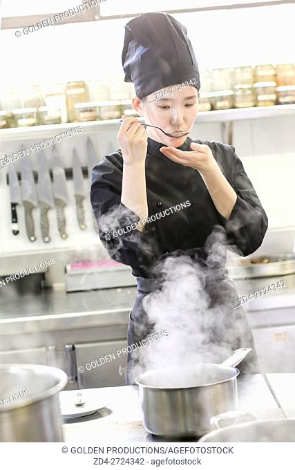 Chef tasting food in restaurant kitchen
