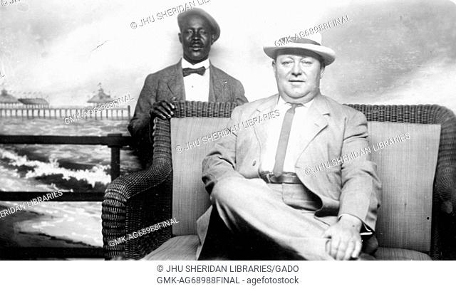 Half length sitting and standing portraits of mature white male and mature African American male, white male wearing light suit with dark tie and hat