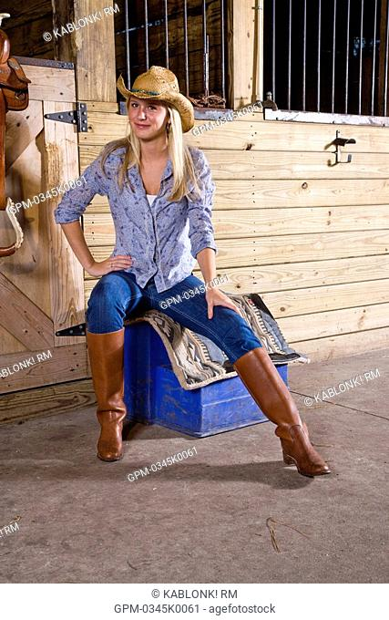 Teenage girl in stable with saddle wearing cowboy hat and boots