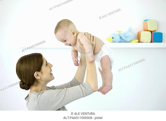 Mother lifting baby in the air, both smiling at each other