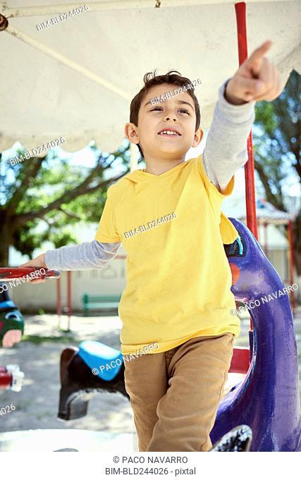 Hispanic boy on carousel at playground