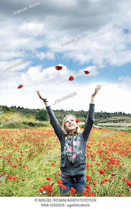 Blonde teen girl throwing flowers in the wind