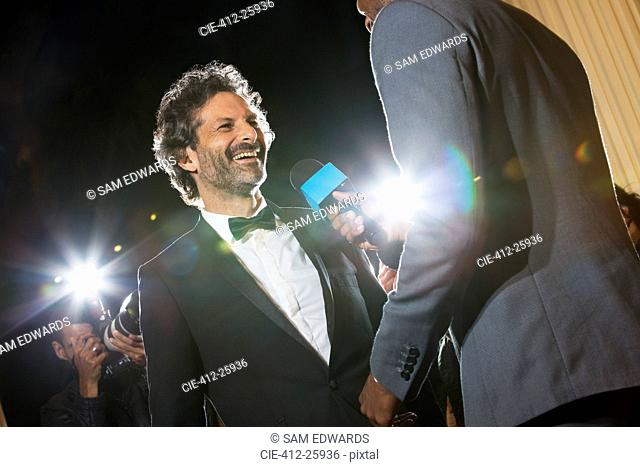 Smiling celebrity being interviewed and photographed by paparazzi at event