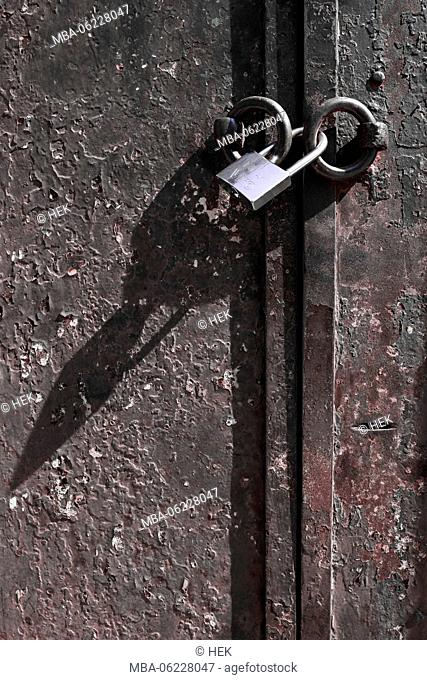 A padlock casts its shadow on a rusted steel door