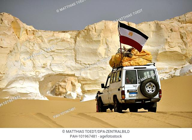 A Toyota Landcruiser SUV crosses a sand passage in front of a limestone formation in the Way Desert at Farafra, taken on 20.04