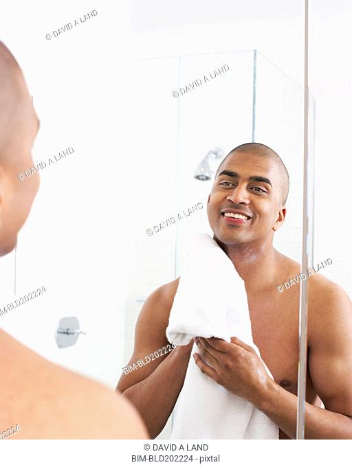 Man in bathroom wiping face with towel