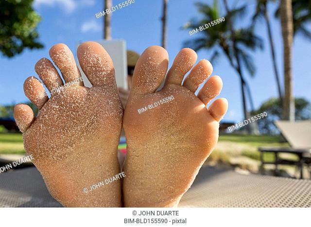 Close up of bottom of sandy feet of Caucasian woman