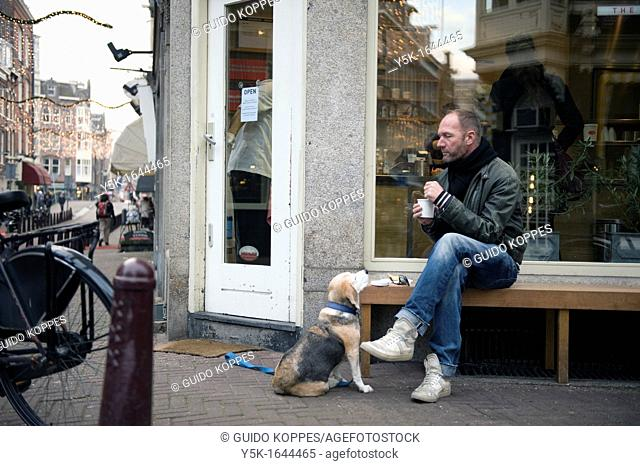 Amsterdam, Netherlands. Man eating soup for lunch in front of the shop, selling quick meals