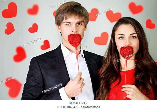 Man and woman holding a heart on a stick