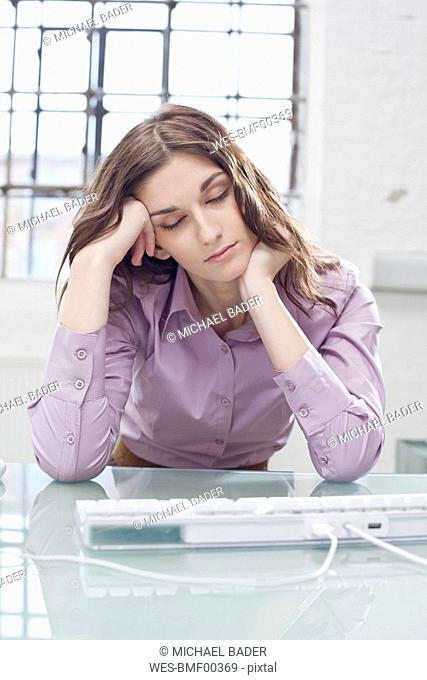Young businesswoman sitting in office, eyes closed