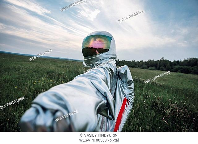 Spaceman exploring nature, reaching out hand