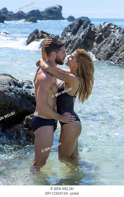 A couple standing in the shallow water along the rocky coast wearing swimwear in an embrace; Tarifa, Cadiz, Andalusia, Spain