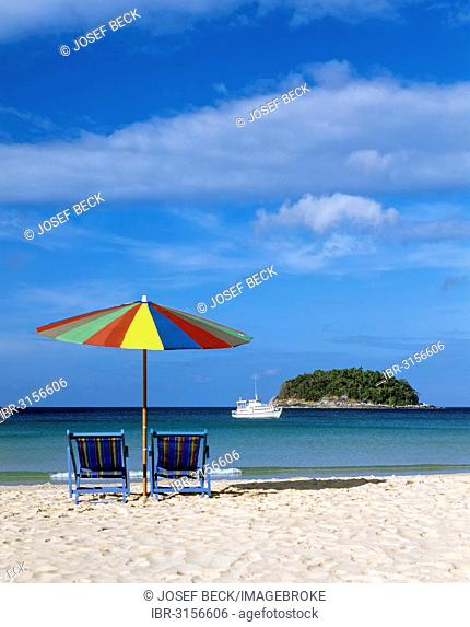 A sunshade with two beach chairs on Kata Beach, and excursion boat and the island of Ko Pu at the back, Andaman Sea