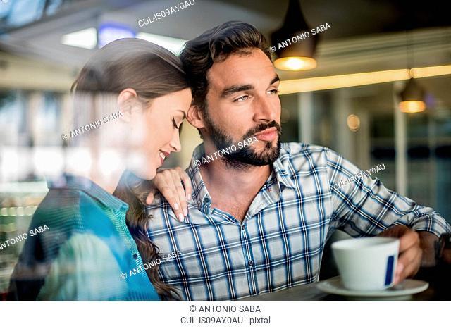 Couple at cafe window seat, Dubai, United Arab Emirates