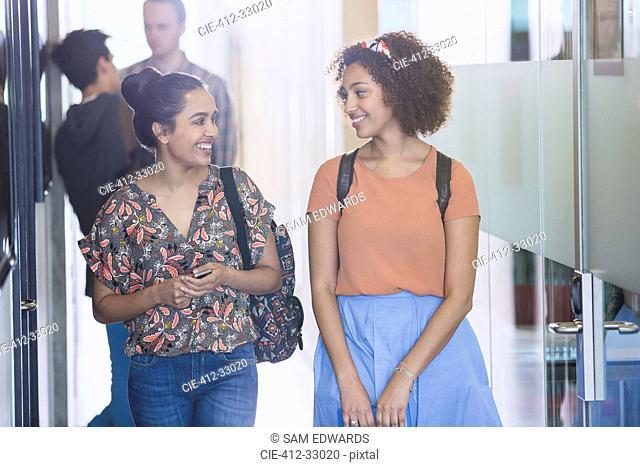 Smiling female college students walking in corridor