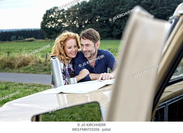 Couple at pick up truck reading map