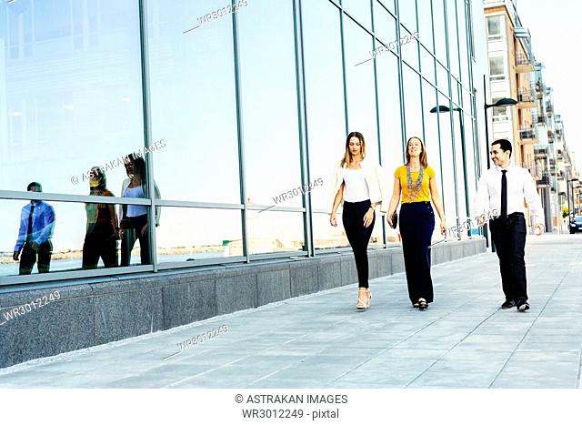 Three colleagues walking in city street