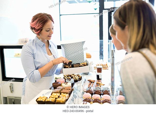 Worker boxing sweets for customer in bakery
