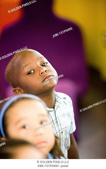 Young children watching and listening attentively in a colorful room