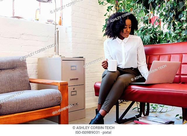 Woman in office sitting on sofa using laptop