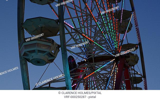 The colorfully illuminated Gentle Giant Ferris Wheel spins against the twilight sky during the 2014 New Jersey State Fair at the Sussex County Fairgrounds in...