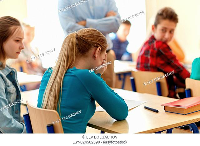 education, high school, learning and people concept - crying student girl with bad test result and teacher in classroom