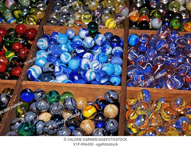his photo has wooden square sections of many multi colored marbles